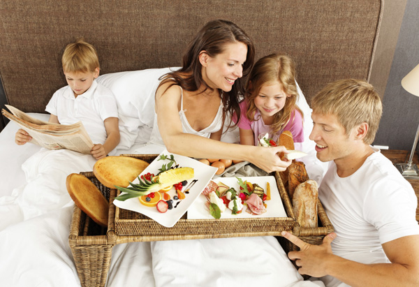 family breakfast in bed boy reading newspaper